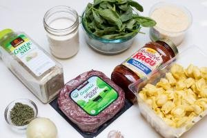 Ingredients on the table including; ground beef, tortellini, garlic cloves, an onion, parsley in a bowl, Ragu pasta sauce, spinach in bowl, parmesan in a plastic container, whipping cream in a jar and garlic salt