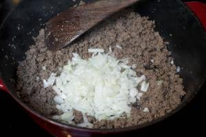 Diced onions and ground beef in a ceramic baking pan