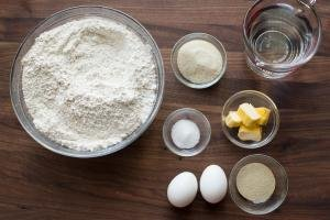 Ingredients on the table including; flour in a bowl, 2 eggs, yeast in a bowl, butter in a bowl, salt in a bowl, sugar in a bowl and water in a measuring cup