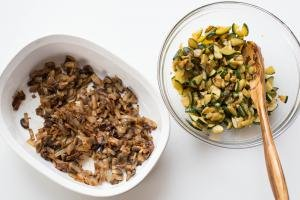 A ceramic baking pan with sautéed mushrooms and onions and a bowl with sautéed zucchini