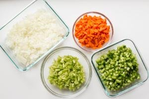 4 bowls with diced celery, green bell peppers, carrots and onions