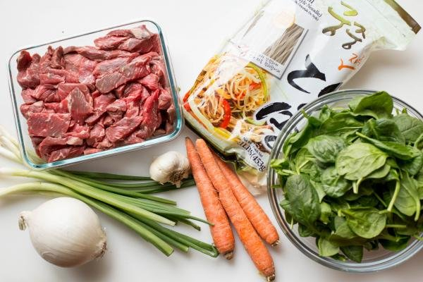 Ingredients on the table including; an onion, garlic, 3 carrots, green onions, spinach in a bowl, beef in a glass container, and sweet potato noodle
