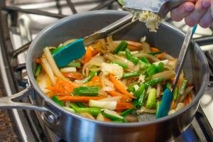 Pot with green onions, yellow onions and carrots having garlic minced into it