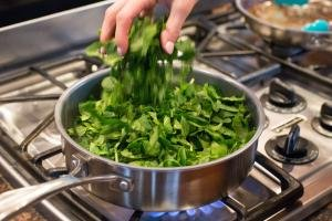 Spinach being added into the pot with sautéing veggies