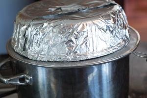 Foil wrapped microwave cover on top of the mesh strainer on top of the steam bath