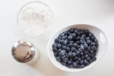A bowl of blueberries, a bowl of flour and sugar on the table