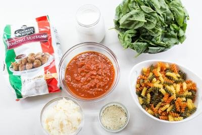 Ingredients on the table including; a bowl with pasta, a bowl with garlic salt, a bowl with parmesan, a bowl of Italian pasta sauce, a bowl of spinach, a jar of whipping cream and a package of homestyle meatballs