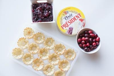 Fillo shells, cranberries in a bowl, Brie cheese in a package, cranberry sauce in a bowl