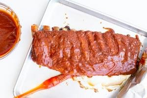 BBQ Ribs on a baking pan being covered in BBQ sauce
