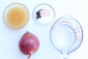 On the table a purple onions, a measuring cup of water, a bowl of apple cider vinegar, and a bowl with seasoning