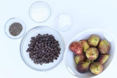 5 bowls on the table with these ingredients; chocolate chips, figs, chia seeds, coconut flakes, and coconut oil