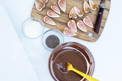 On the table a cutting board with figs, a bowl with chocolate, a bowl with chia seeds and a bowl with coconut flakes