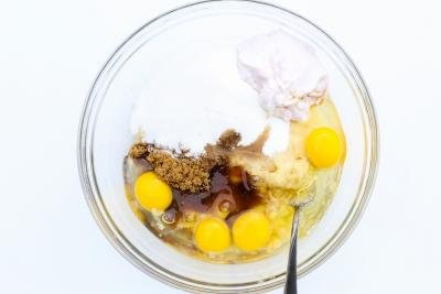 mashed banana, eggs, brown sugar, white sugar, vanilla extract and yogurt in a bowl with a fork