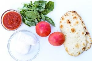 Ingredients on the table including; 2 tomatoes, basil, mozzarella cheese in a bowl, tomato sauce in a bowl and flatbread