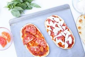 Pizza sauce spread on the flatbread that is on the baking pan, also tomatoes added to both flatbreads and one has mozzarella on it
