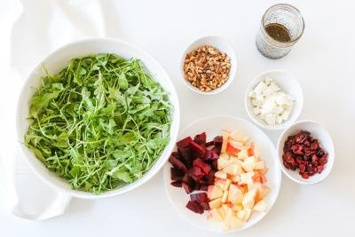5 bowls the table with the following ingredients; arugula, walnuts, goat cheese, dried cranberries, apples and beets and a jar with dressing