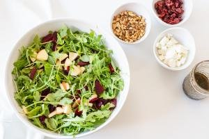 A bowl with the salad mixture, a bowl with goat cheese, a bowl with walnuts, a bowl with dried cranberries and a jar with dressing on the table