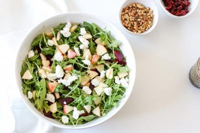 A bowl with the salad mixture goat cheese on top, a bowl with walnuts, a bowl with dried cranberries and a jar with dressing on the table