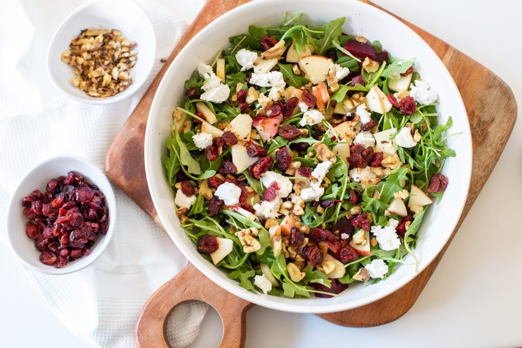 Beet and Goat Cheese Arugula Salad in a bowl with a bowl of dried cranberries and a bowl of walnuts besides it
