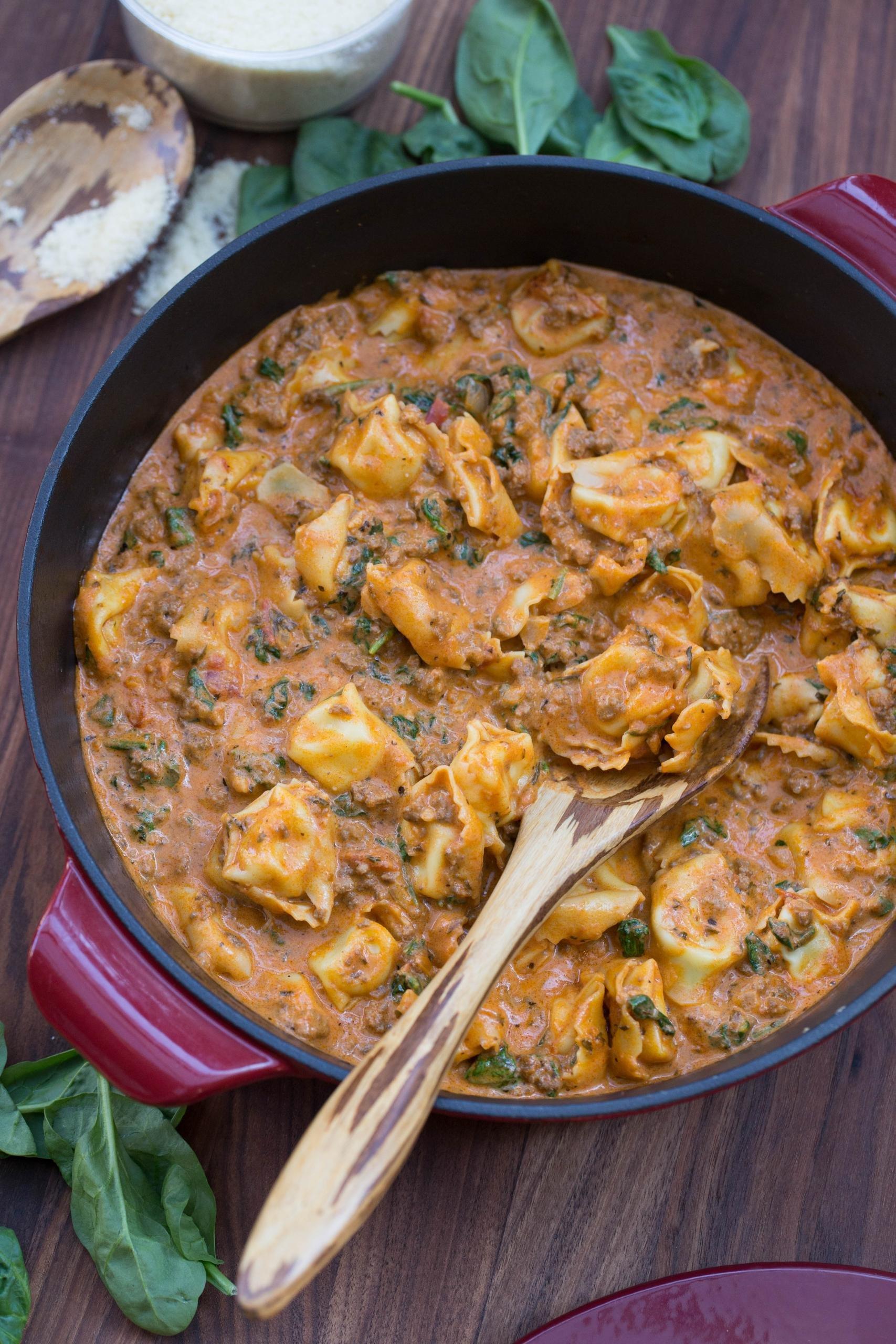 Creamy Spinach Tomato Tortellini in a ceramic baking pan