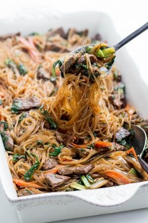 Korean Stir-Fried Sweet Potato Noodles in a serving tray being lifted with a spoon
