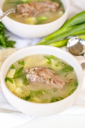 Cooked turkey neck in a bowl of soup.
