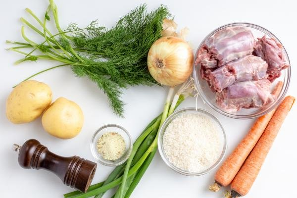 Ingredients on the table including; a bowl of turkey necks, 2 carrots, green onions, a bowl of rice, a bowl of seasoning, pepper, 2 potatoes, an onion and dill
