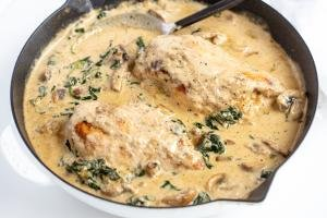 Skillet with chicken in a creamy sauce.