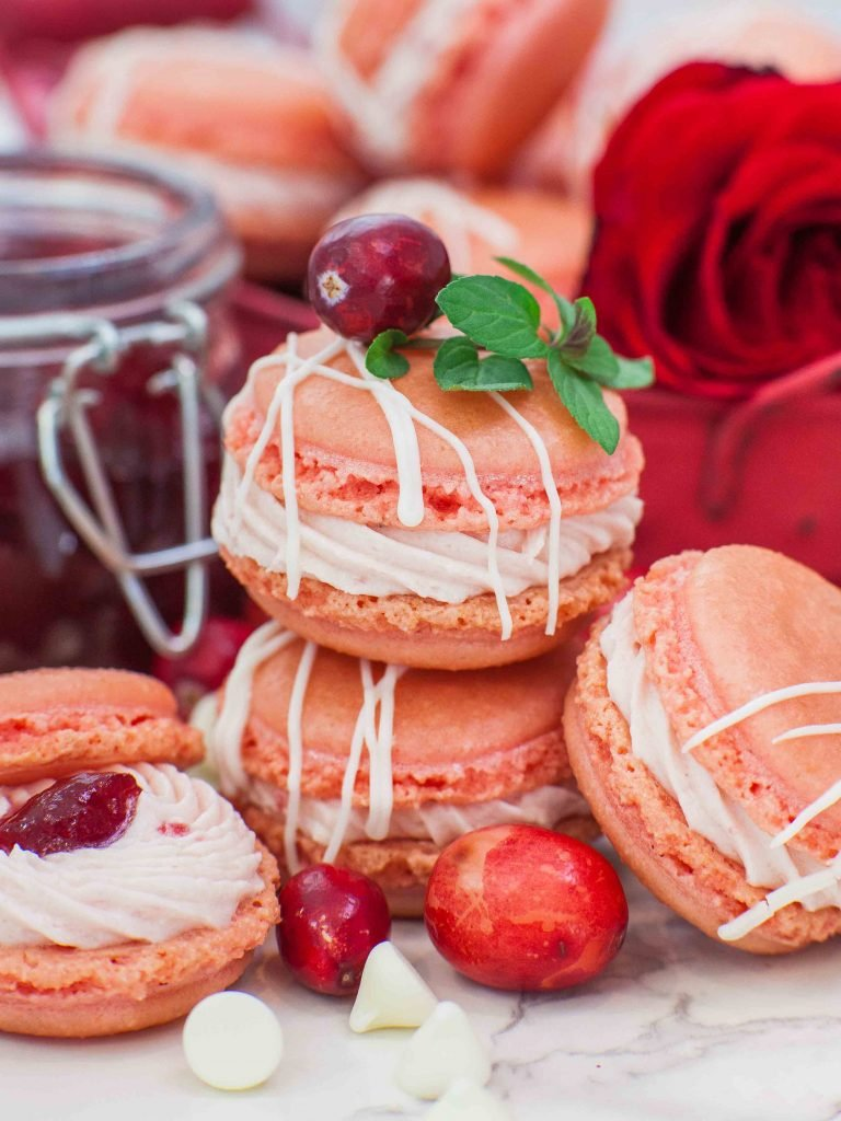 Four macarons with jam and rose in the background.