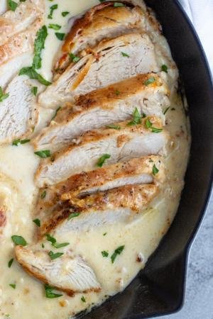 Chicken in a skillet with creamy sauce