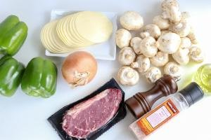 Ingredients (bell peppers, mushrooms, beef, cheese, onion and seasoning) on a cutting board