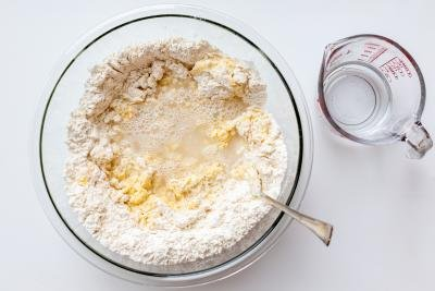Flour, eggs and water in a bowl with flour