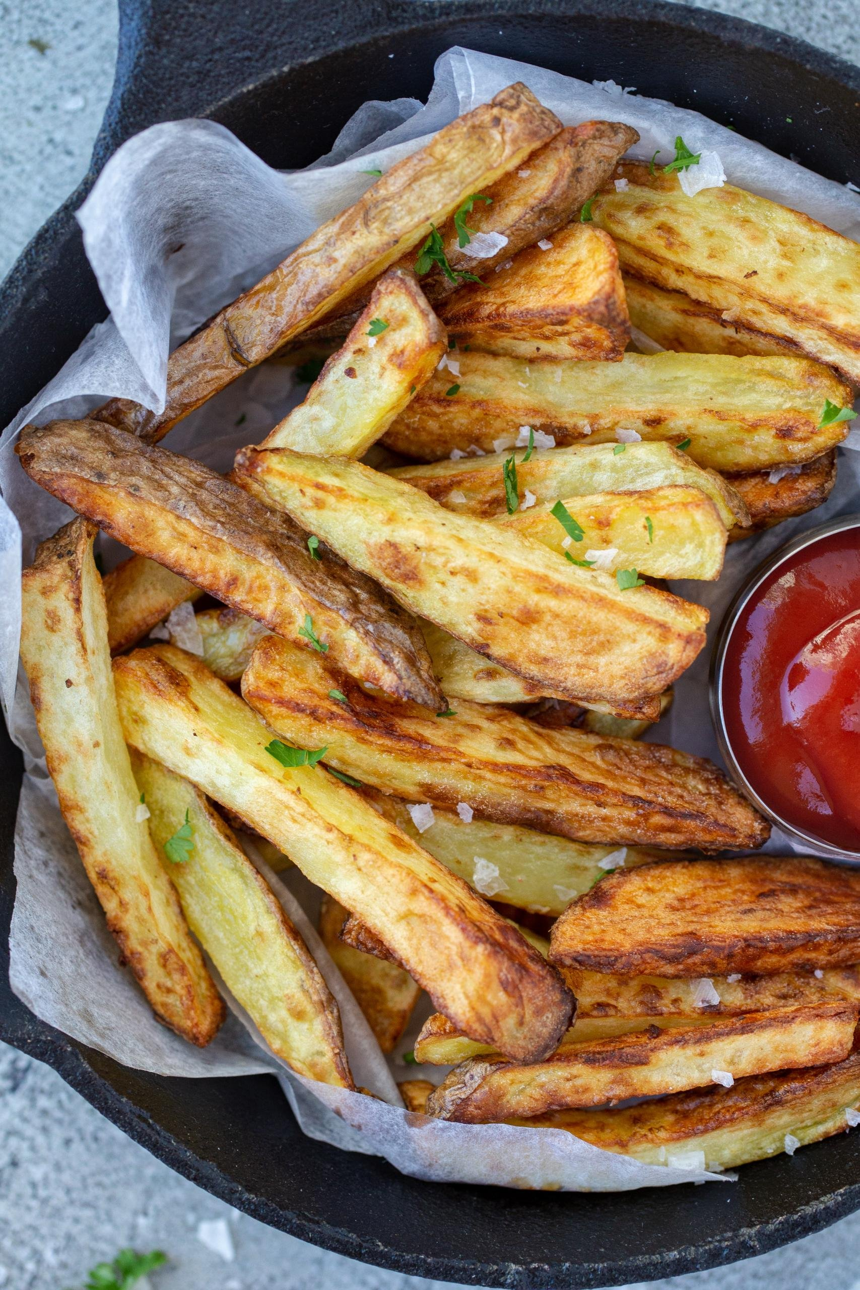 Air fryer french fries in a plate with ketchup