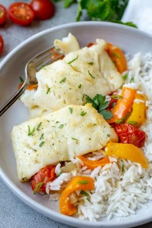 Plate with baked cod and plate with rice