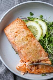 Air Fryer Salmon in a plate with greens
