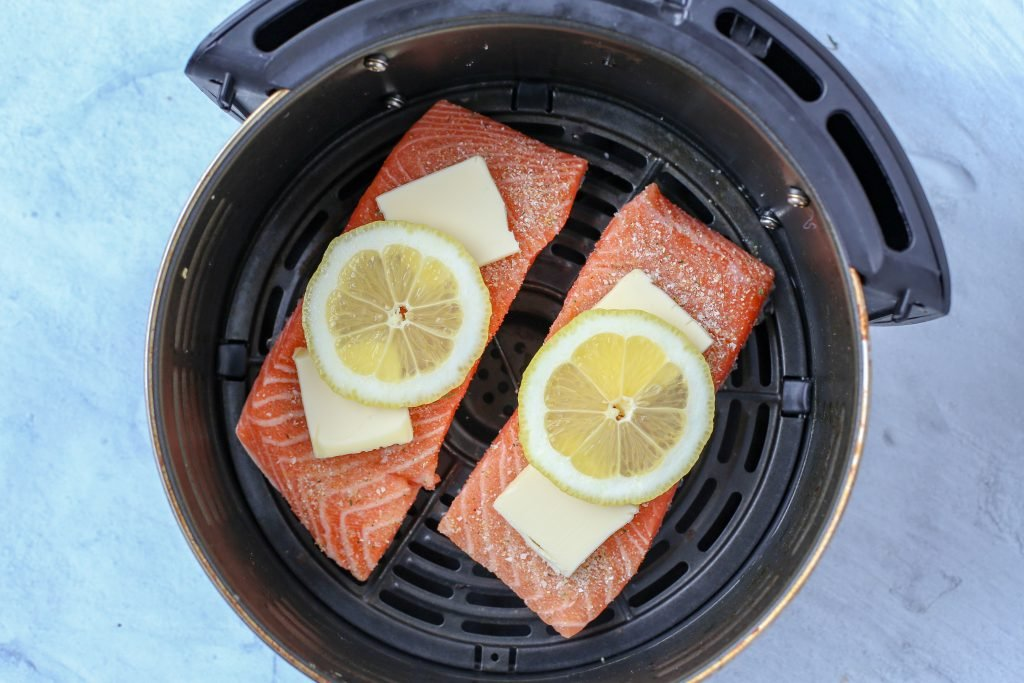 Salmon in a airfryer basket with butter and lemon