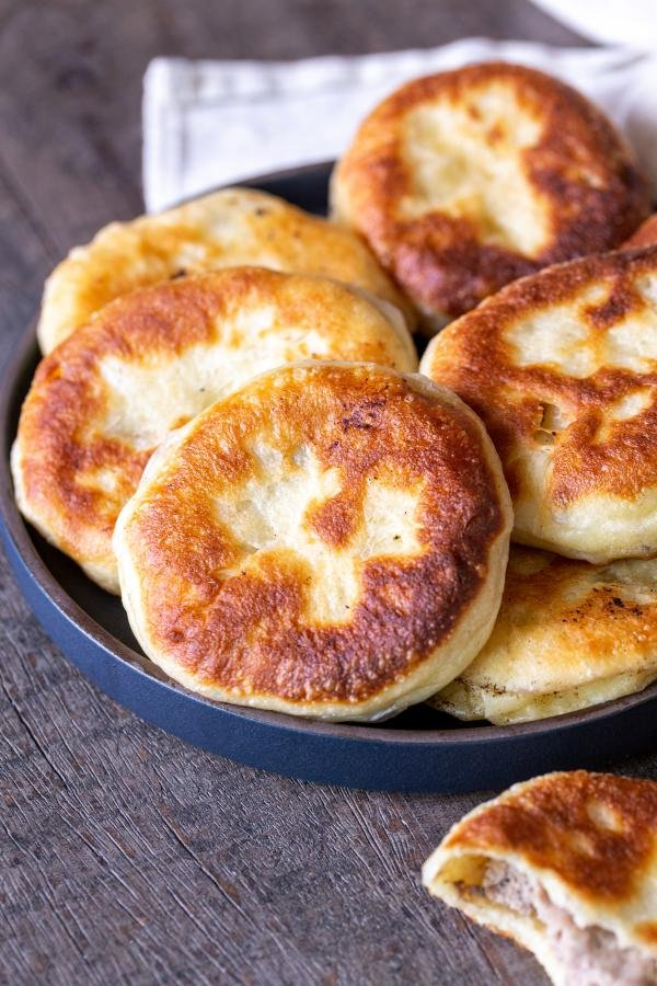 Piroshki in a bowl with another one next to the bowl