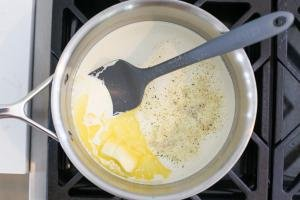 Pot with cream butter and seasoning on a cook top
