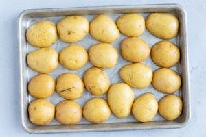Half cut Potatoes on a baking sheet