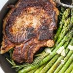 Cooked Ribeye in a cast iron skillet with asparagus