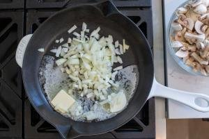 pan with butter and onion and mushrooms next to it
