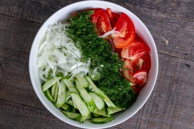 Sliced cucumbers, tomatoes, onion and dill in a bowl.