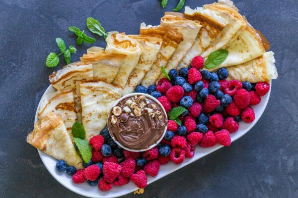 Crepes on a tray, berries and nutella