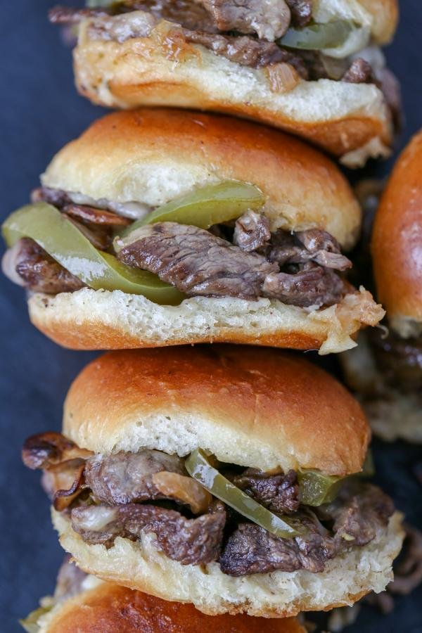Philly Cheesesteak Sliders stacked on a board