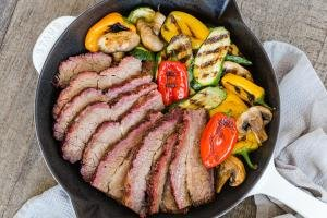 Brisket in a skillet with grilled veggies