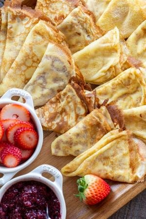 a pile of crepes on a tray with berries and jam