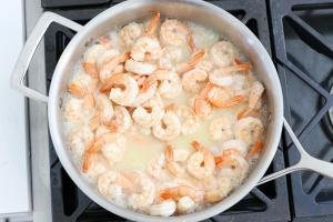 Cooking shrimp in a skillet with sauce