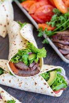 Flank wraps and a tray with veggies and flank in background
