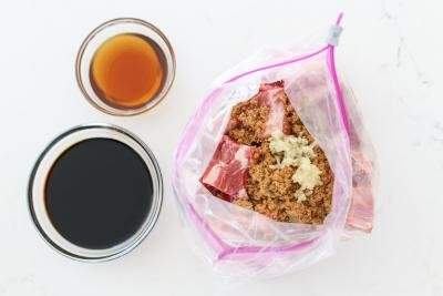 Ziplock bag with with ribs and marinade soy case and sesame oil in a bowl