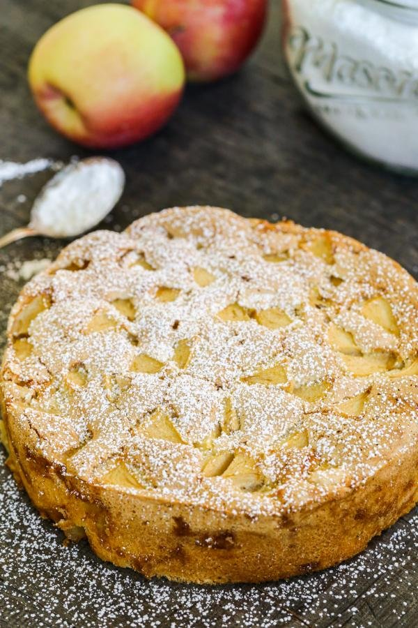 Apple cake on the counter with powdered sugar